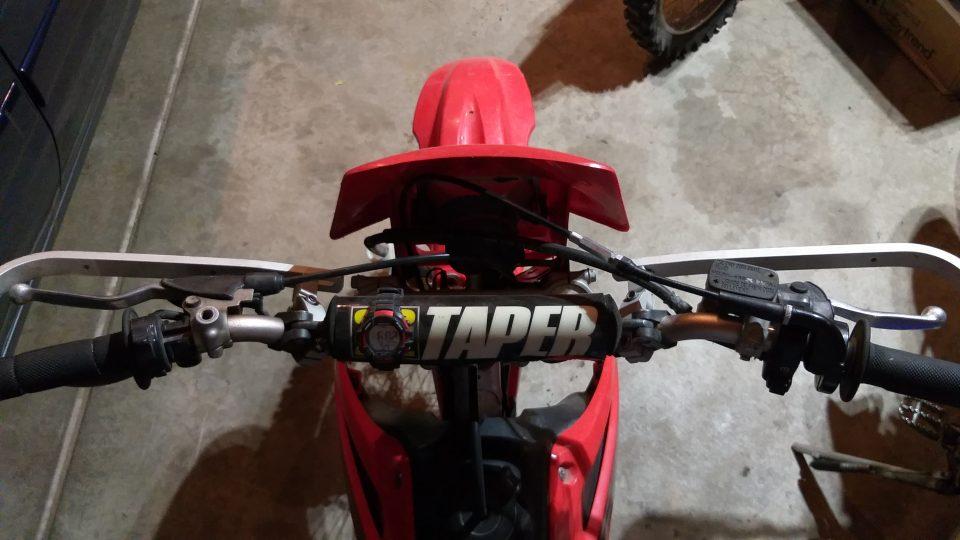 Dirt bike handlebar controls; clutch on left, front brake on right.